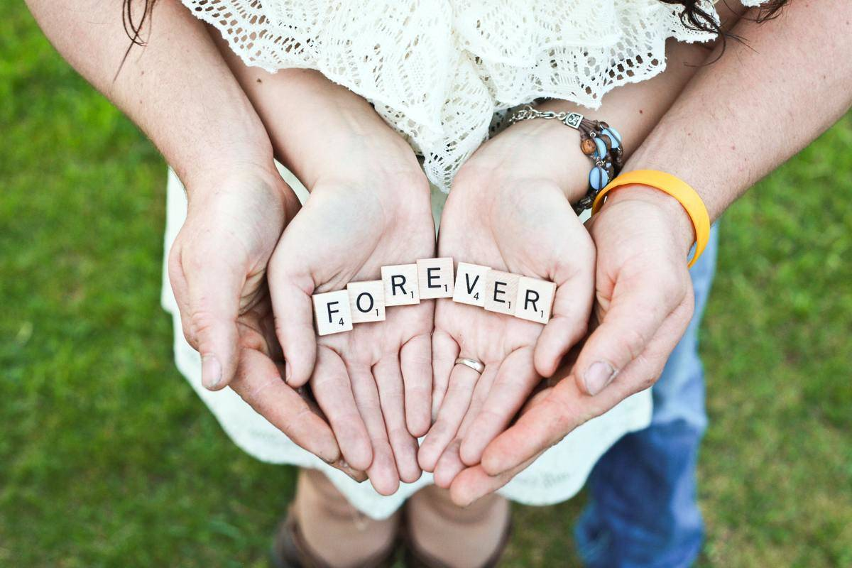 couple hands overlapped with scrabble tiles that spell out