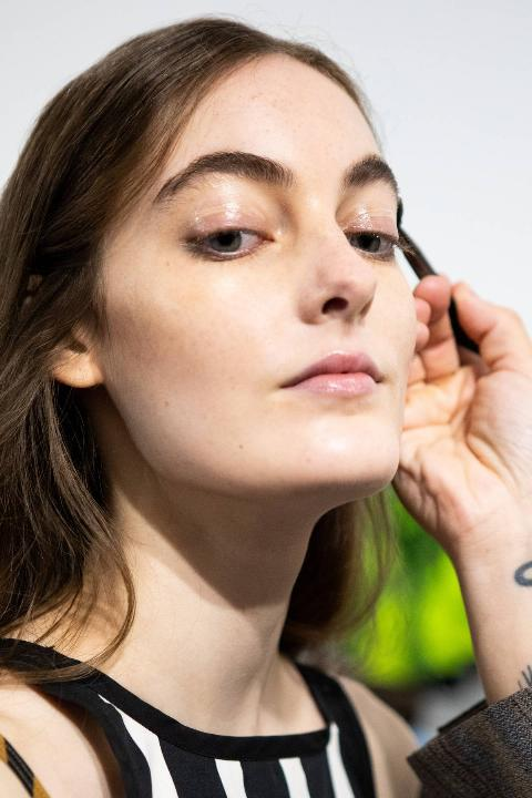 make up artist does the final touch of gel eyebrow during the line up before the show is seen backstage at the Shi.Rt fashion show during the Milan Women's Fashion Week on September 27, 2020 in Milan, Italy.