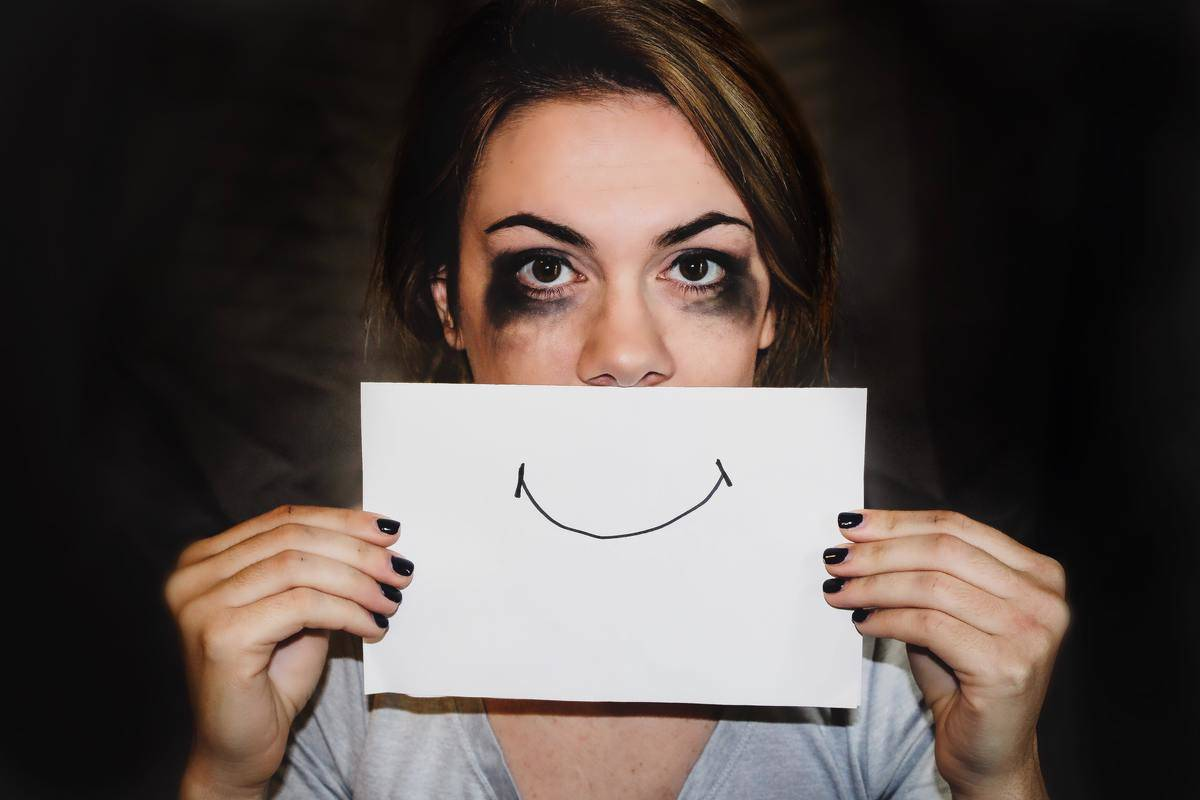 woman with messy makeup holding paper with drawn-on smile over  the bottom half of her face