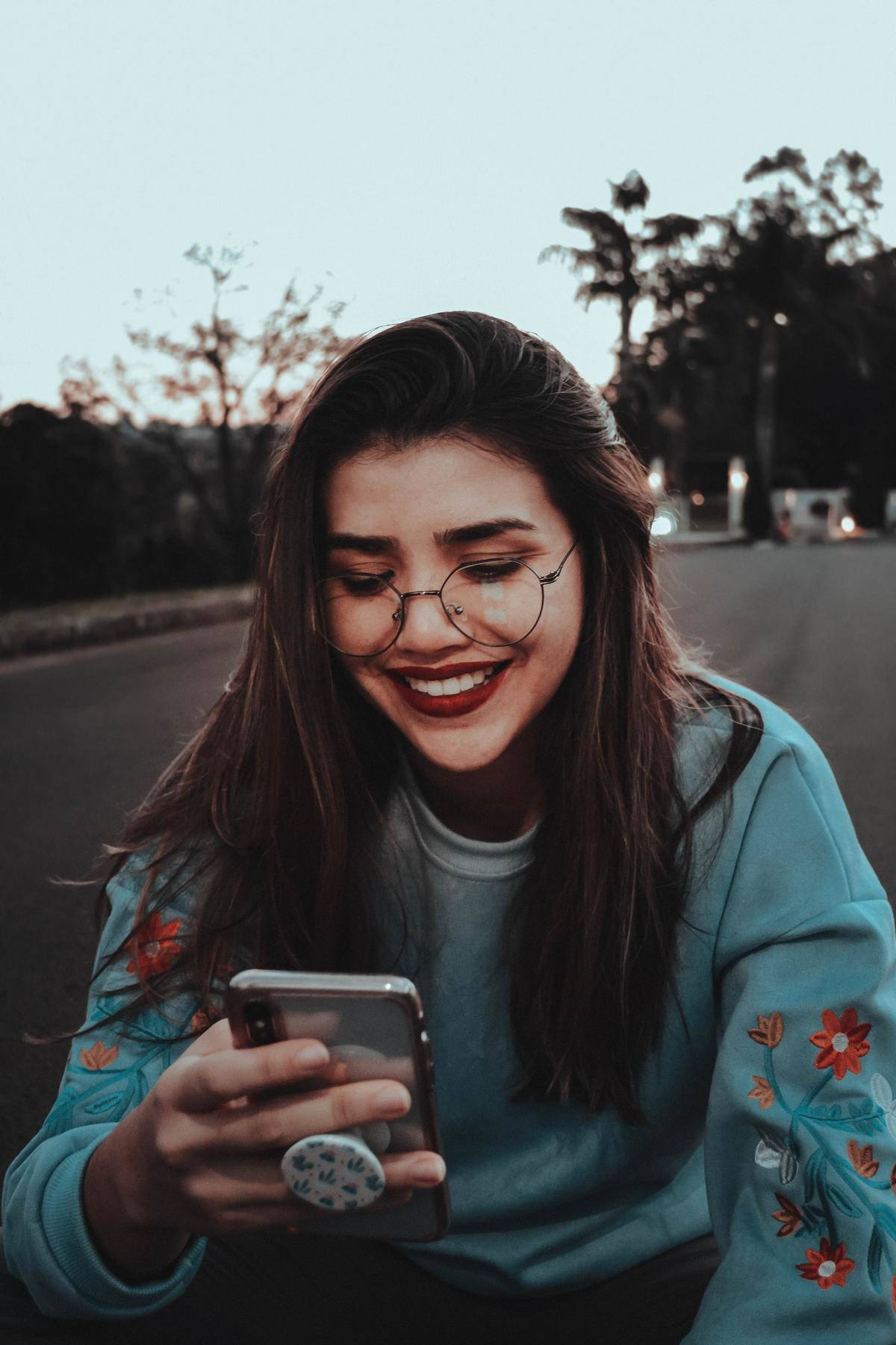 a woman looking down at her phone smiling