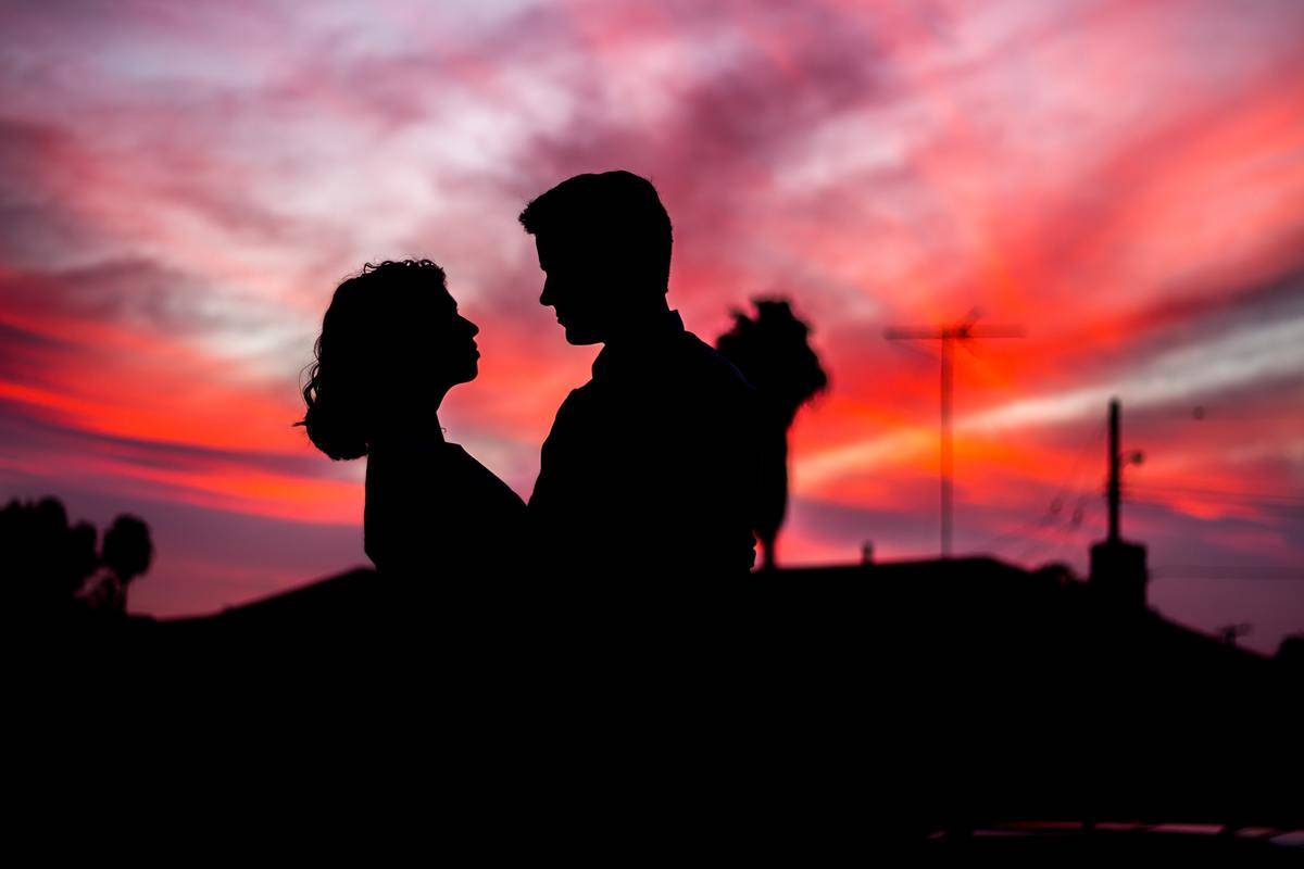 silhouette of couple looking at each other in front of sunset