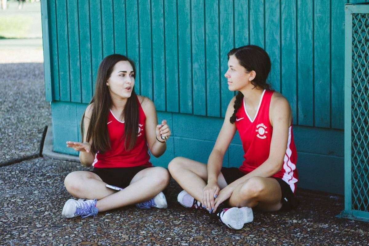 two teen girls sitting on ground in sport uniforms and talking