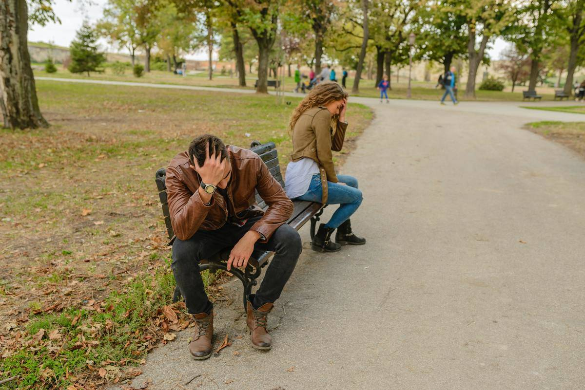man and woman in leather jackets at opposite ends of bench head in hands
