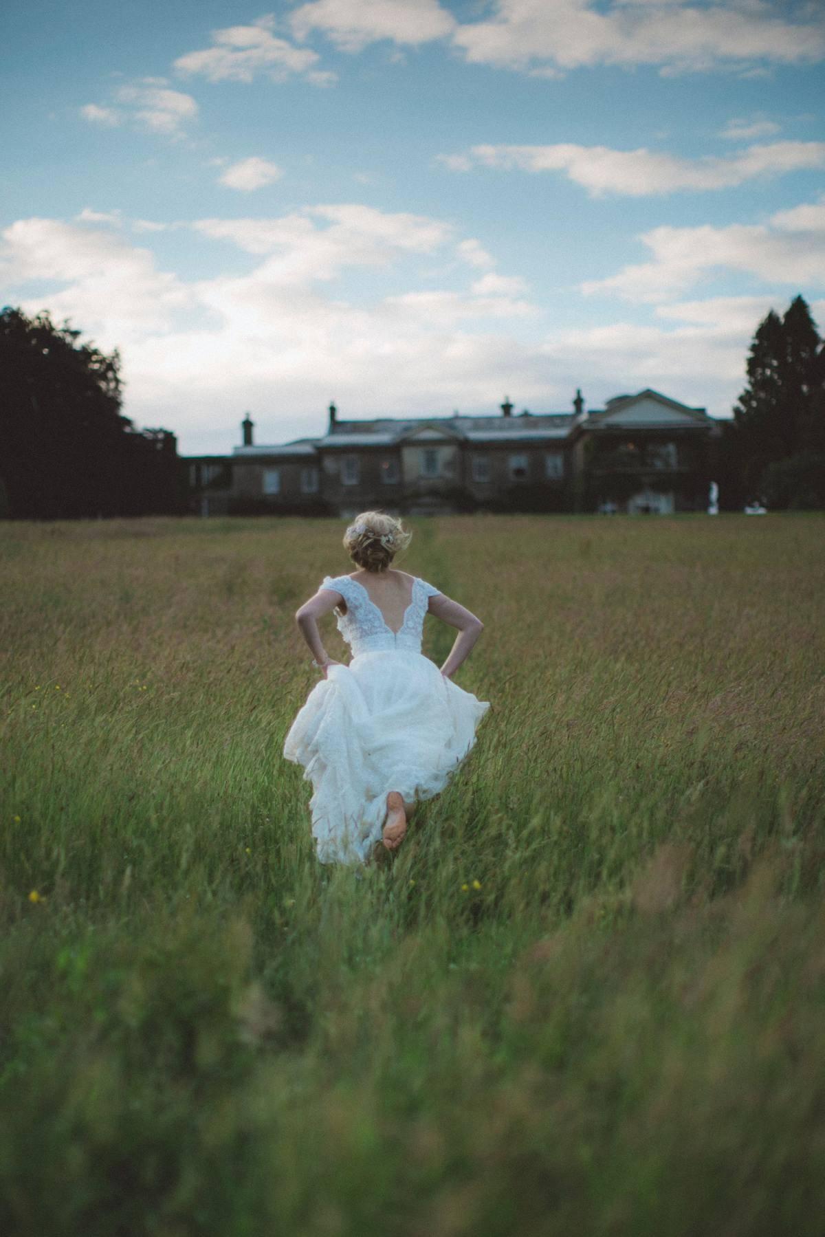 bride running in field barefoot