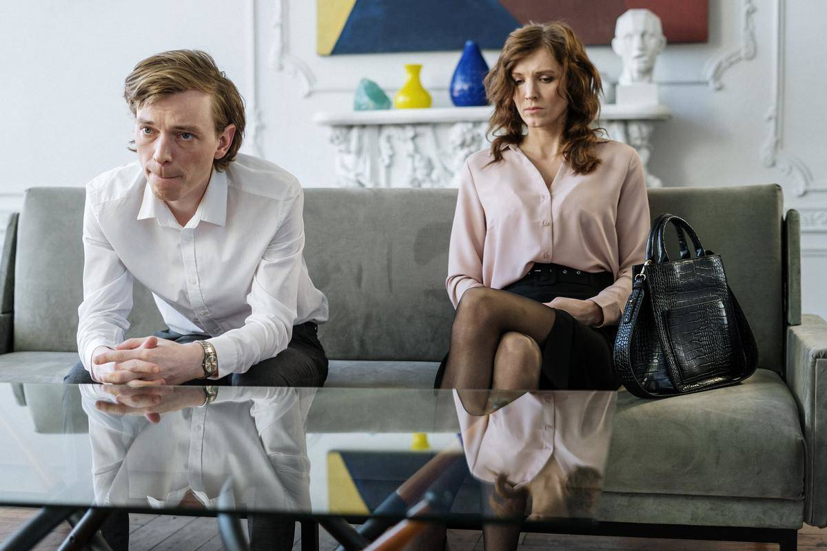 couple sitting on the couch looking sad