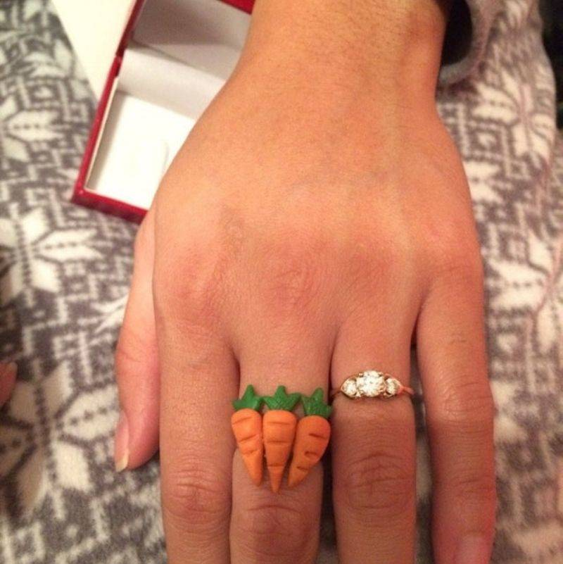 a woman wearing a ring that has three carrots on it