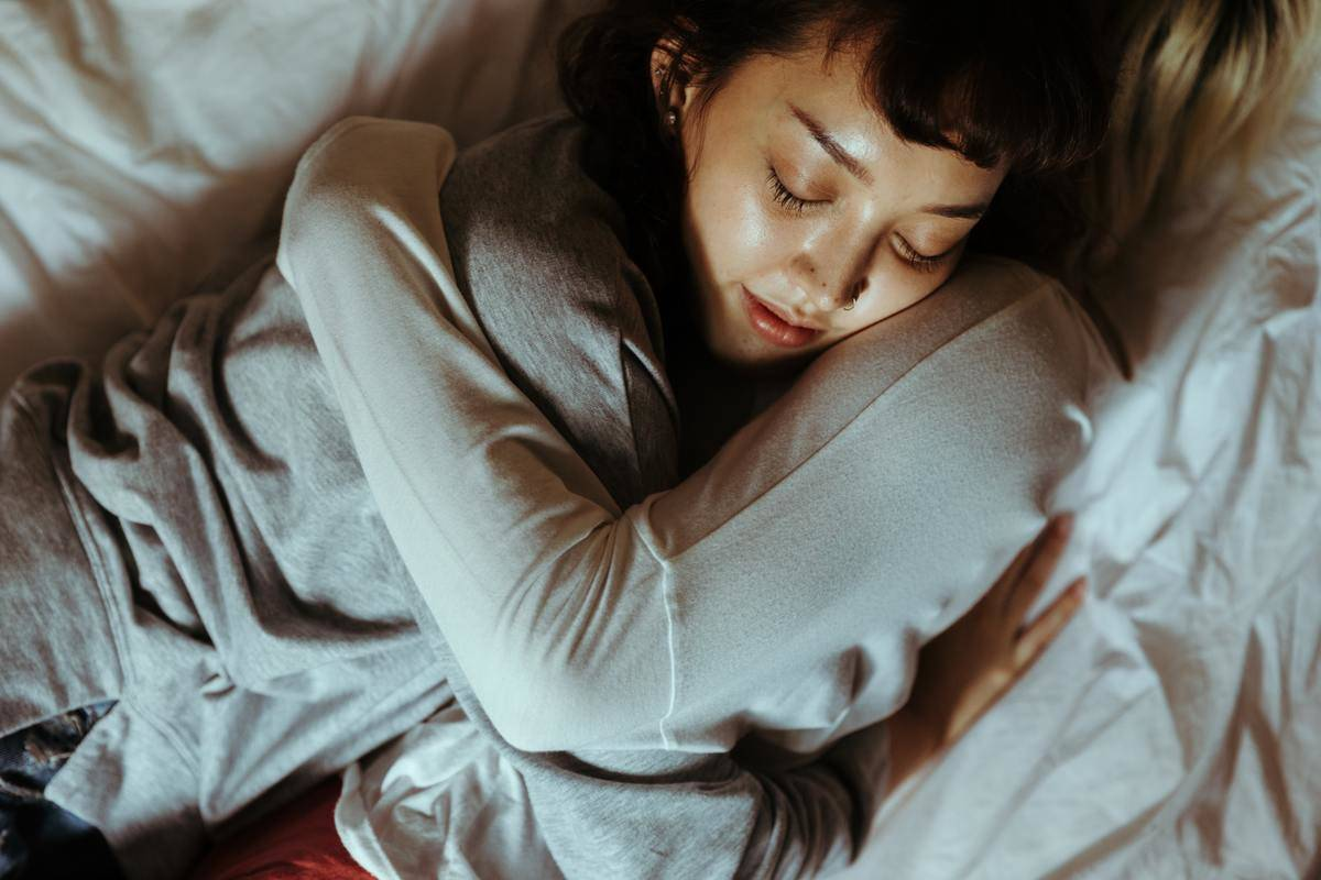 two women hugging in bed