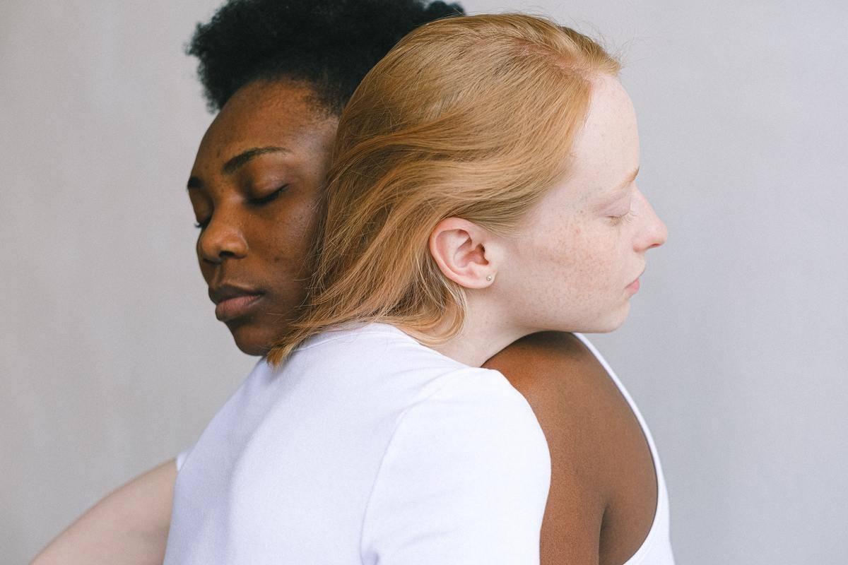 two women hugging heads leaning on shoulders