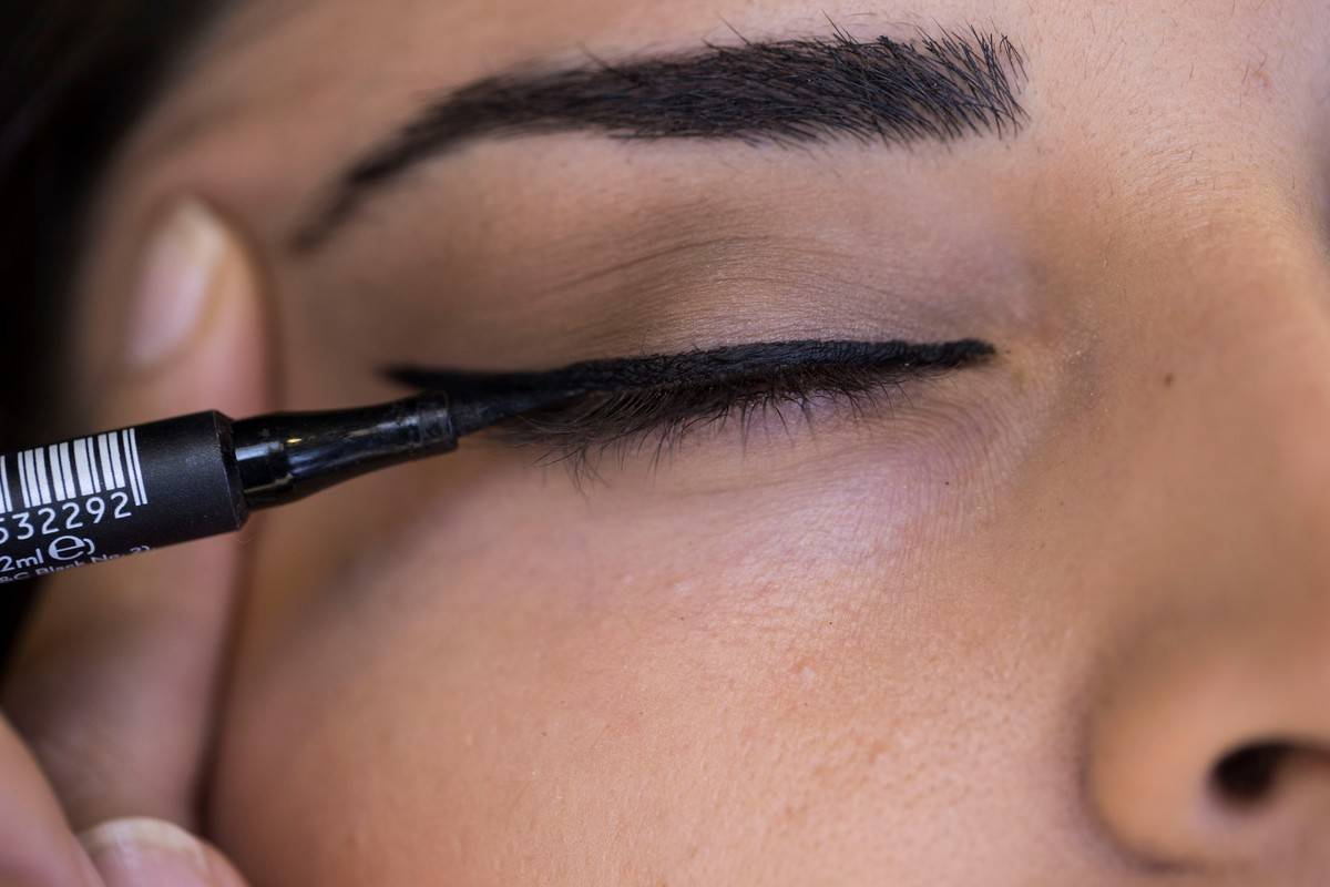A photo shows the close-up brown eye of a woman getting her eyelashes makeup using eyeliner at a make-up and cosmetic products shop in Ankara, Turkey