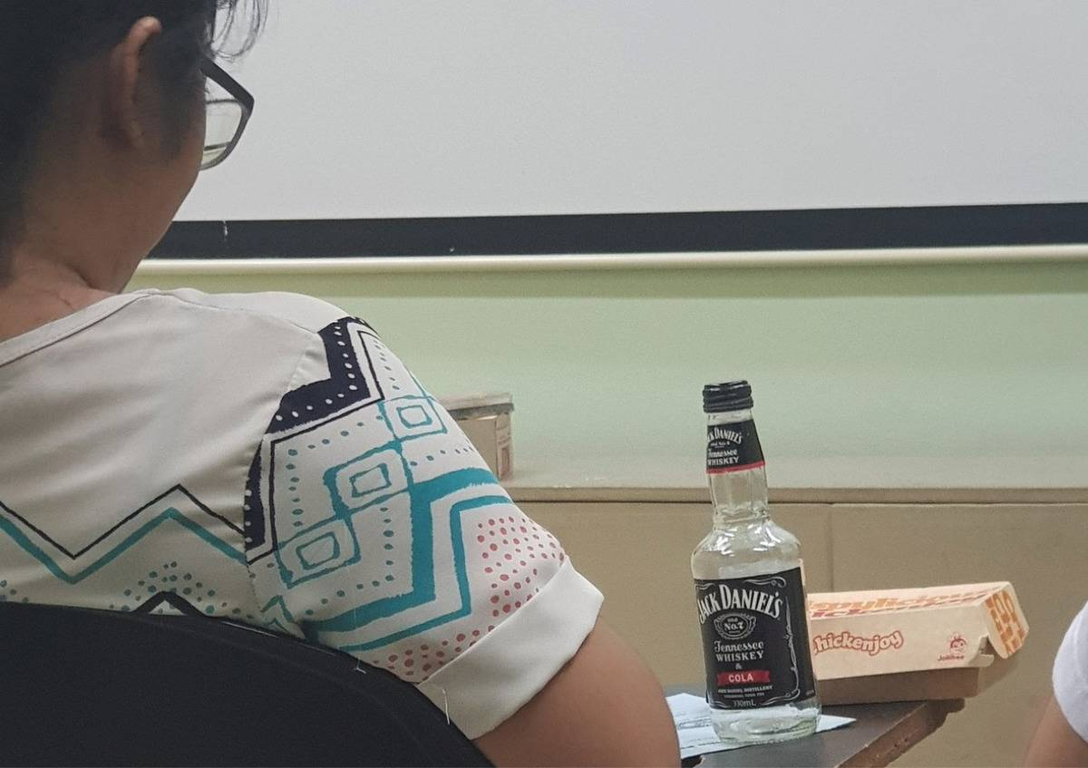 someone eating chicken nuggets and whiskey in class
