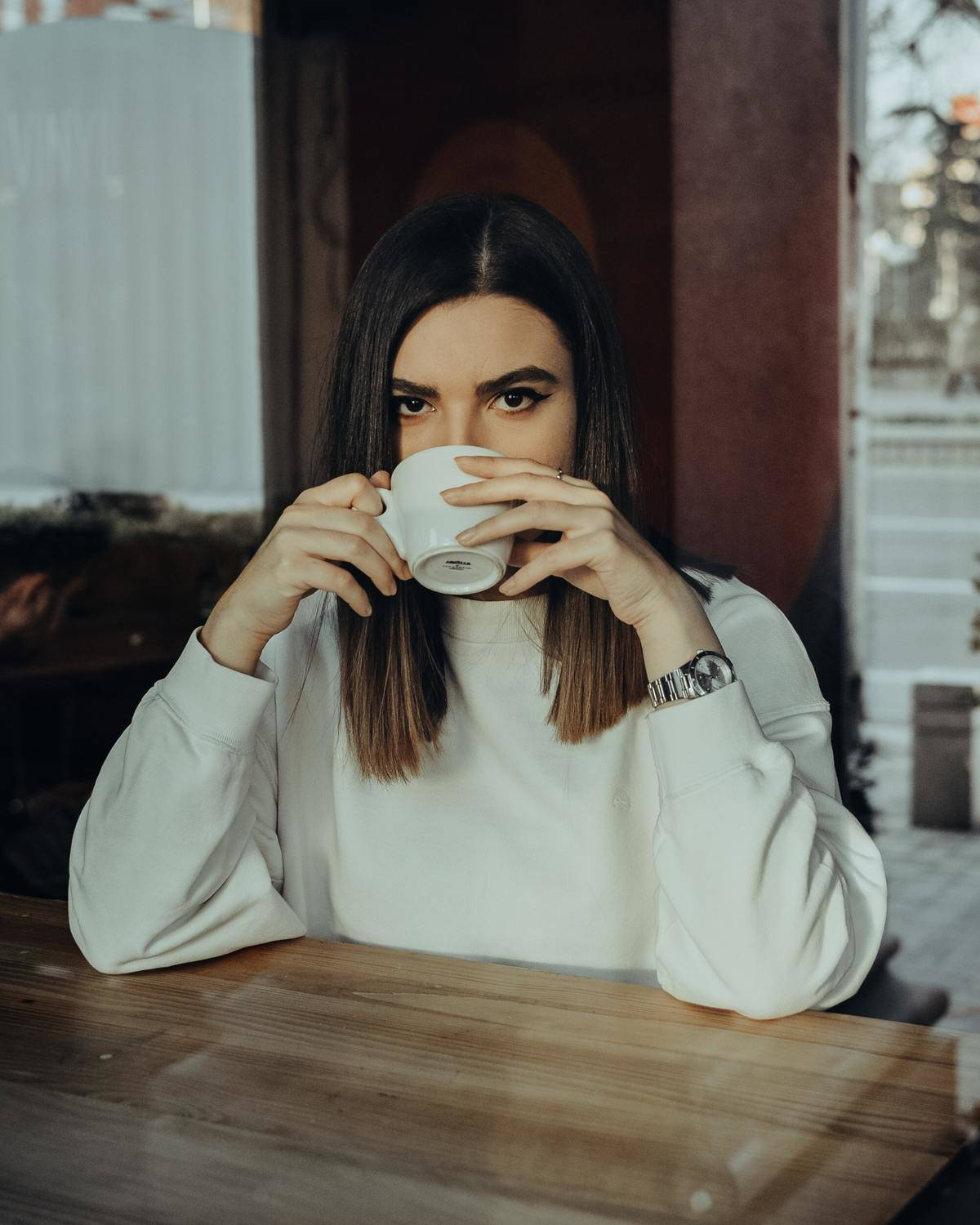 woman drinking cup of coffee and looking into camera