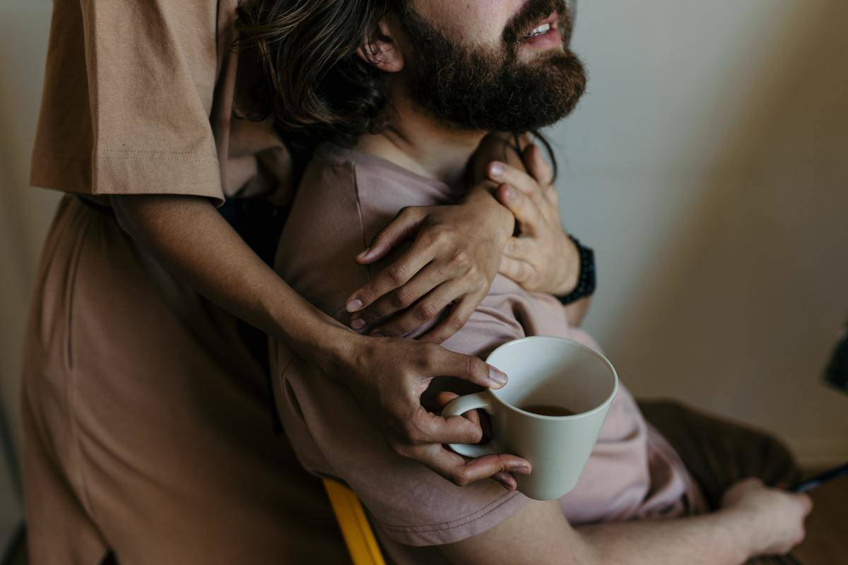 woman hugging man from behind while drinking coffee
