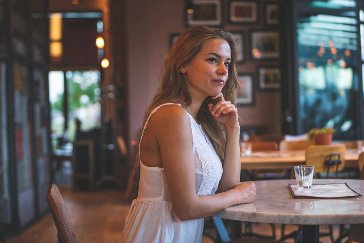 woman in white dress seated at restaurant table alone