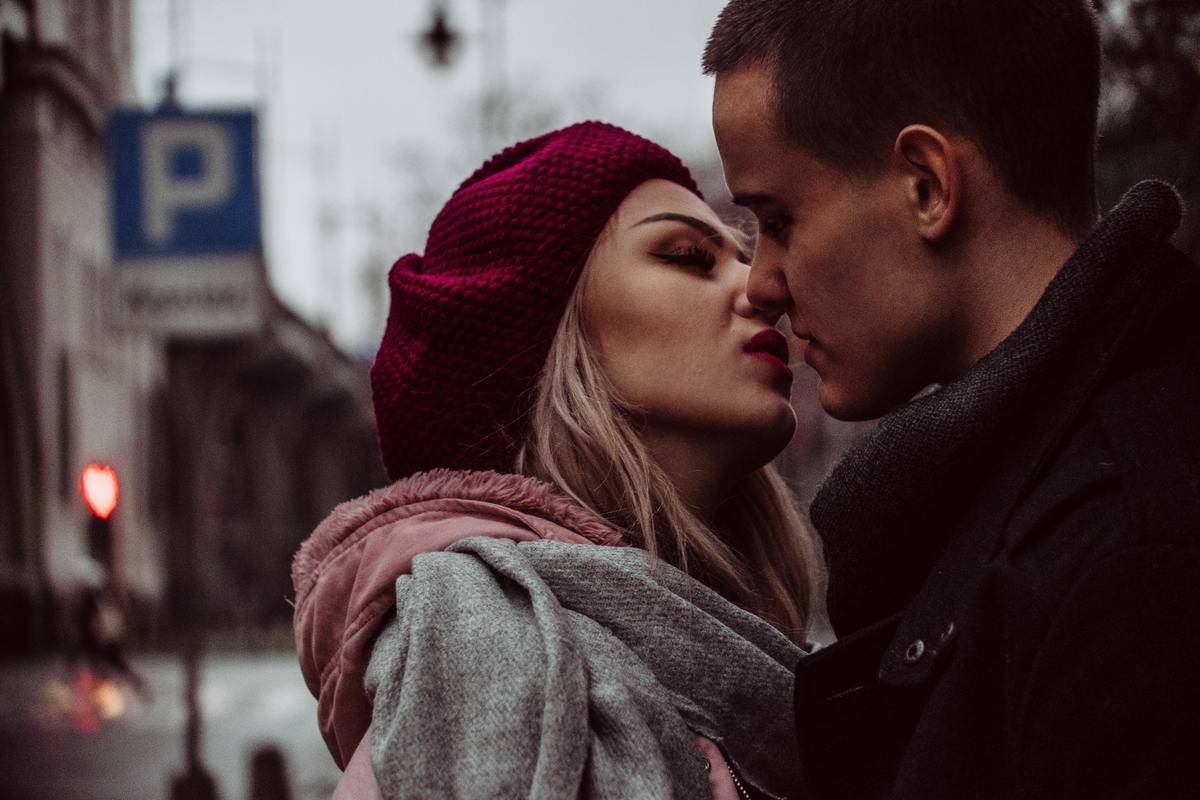 woman leaning in to kiss man on the street