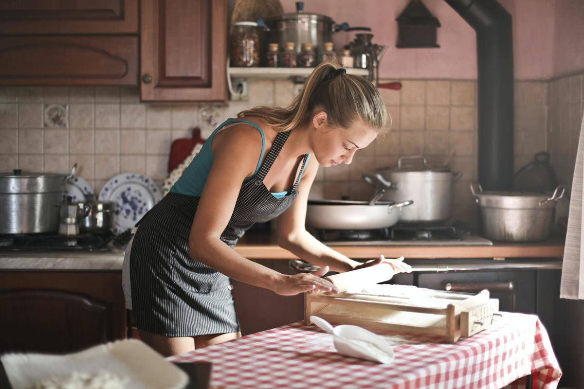 woman wearing apron leaning over pastry in kitchen