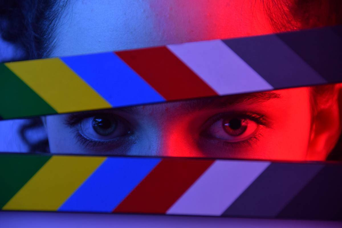 woman looking through movie clapboard in red lighting