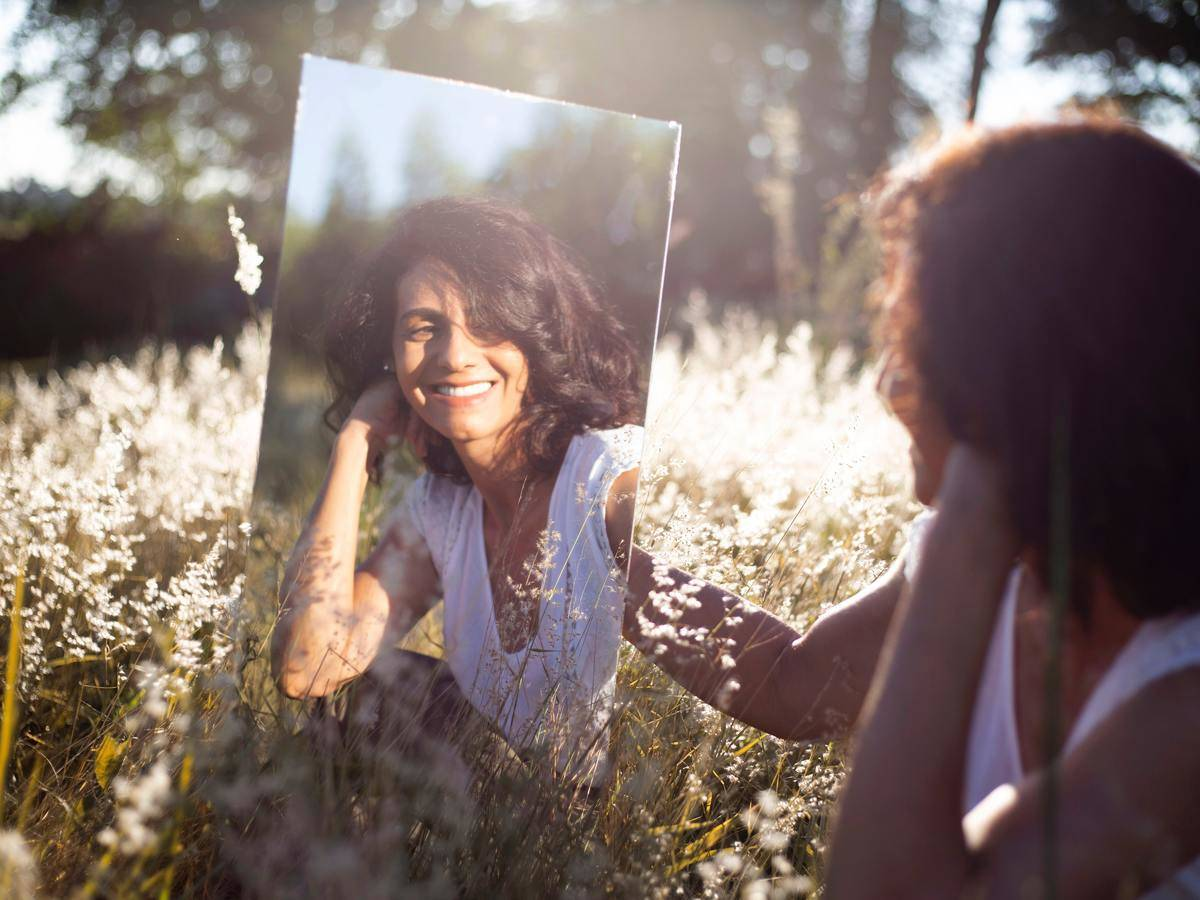 woman looks in mirror in a field