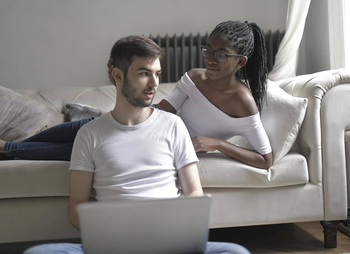 woman lying on couch talking to man seated on couch leaning with lapotp