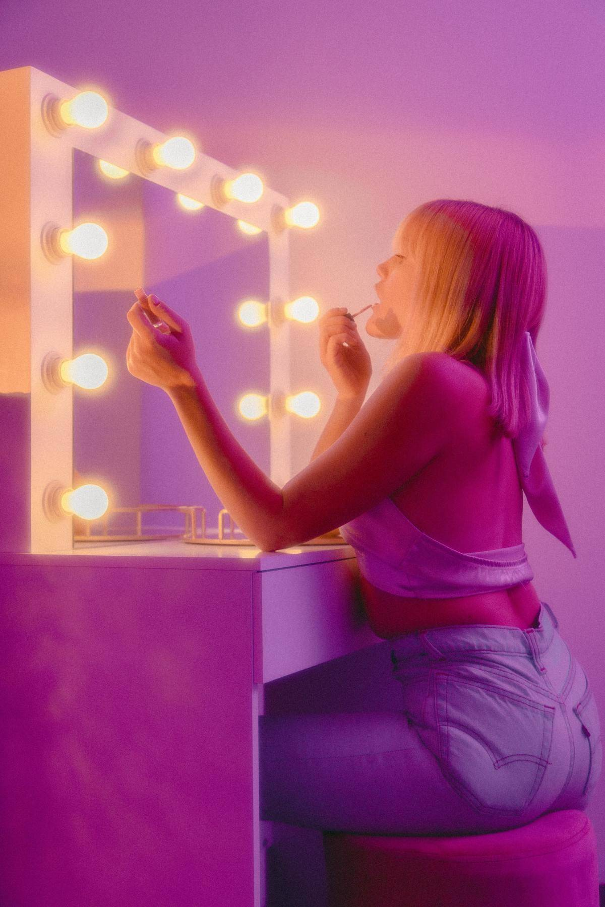 woman putting makeup on in dresser mirror