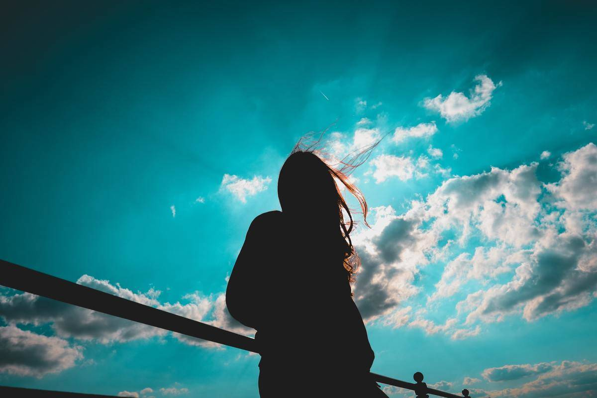 silhouette of woman against radiant blue sky