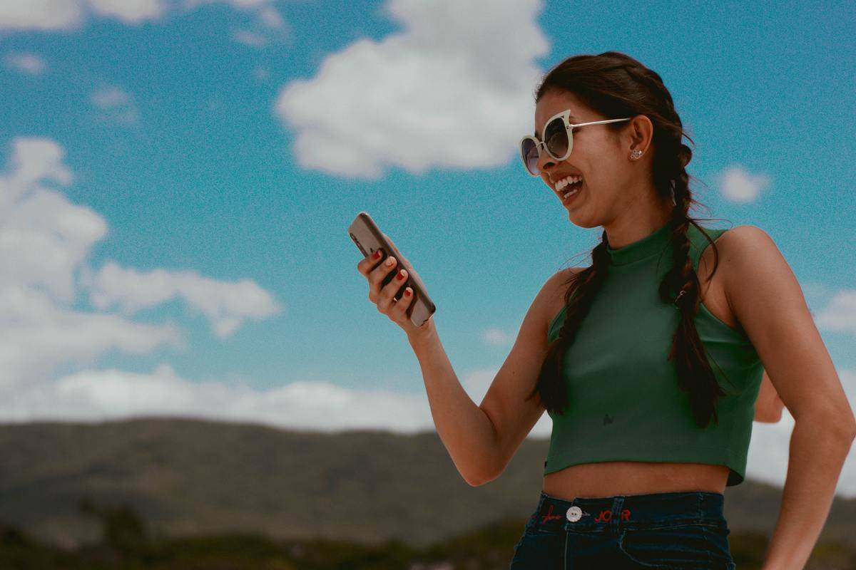 woman texting outdoors and laughing