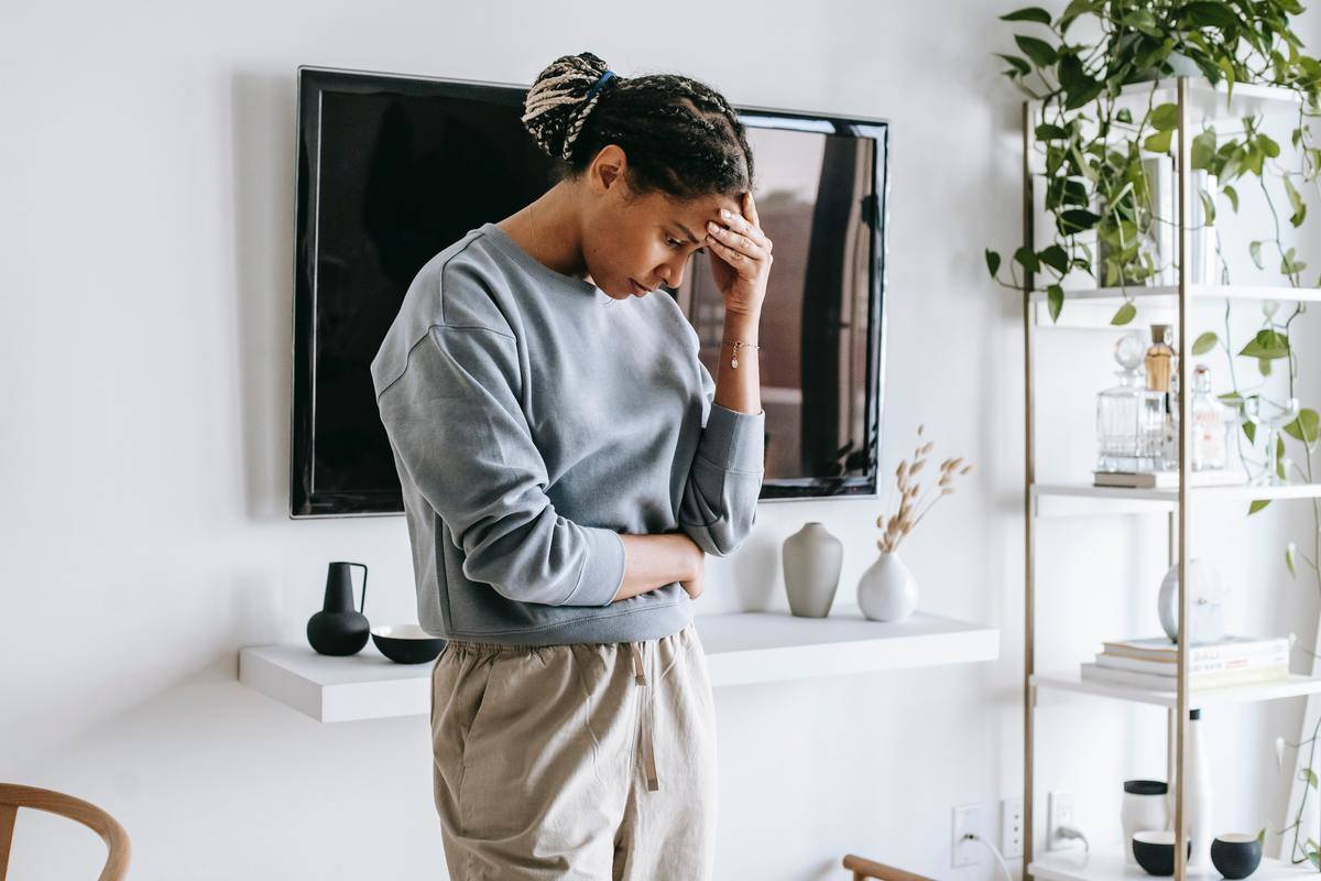 woman standing in living room leaning head in hand
