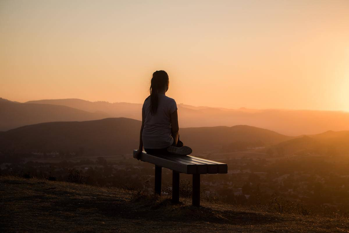 woman seated on bench in sunset