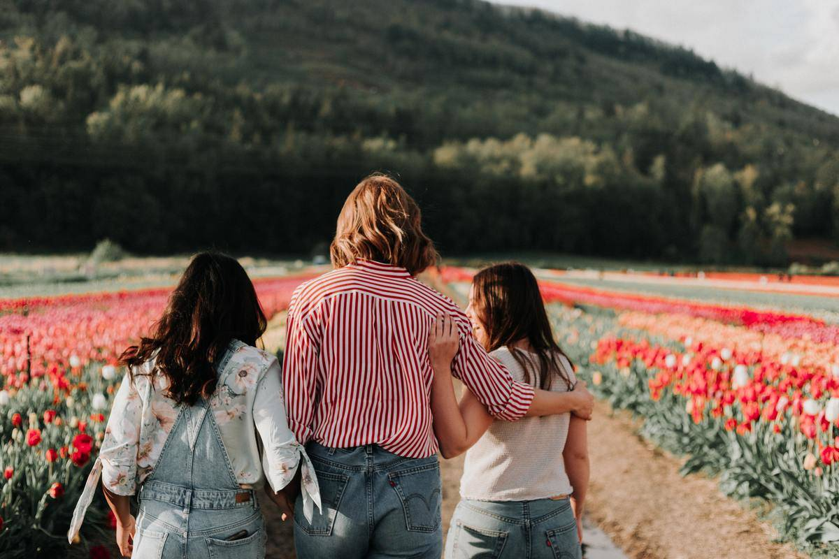 three women walking through flower field