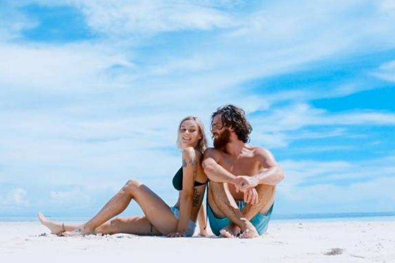woman sits against man on the beach