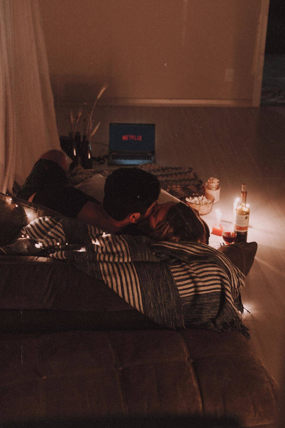 couple kissing on couch while watching Netflix
