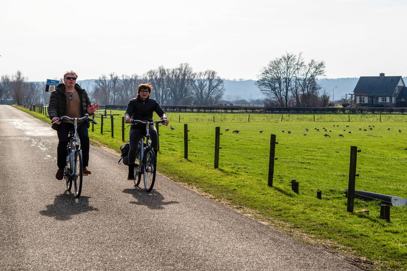 A couple biking while enjoying the sunshine