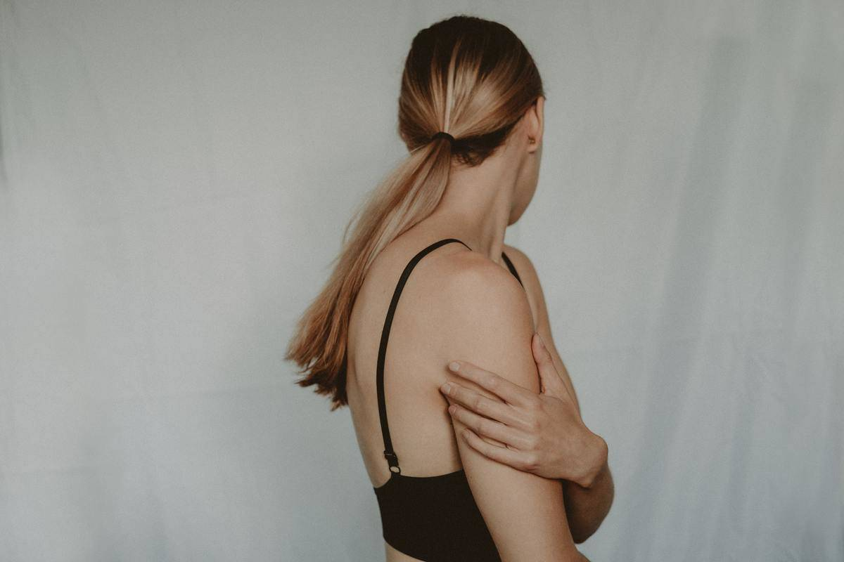 woman holding her arm and looking away from the camera