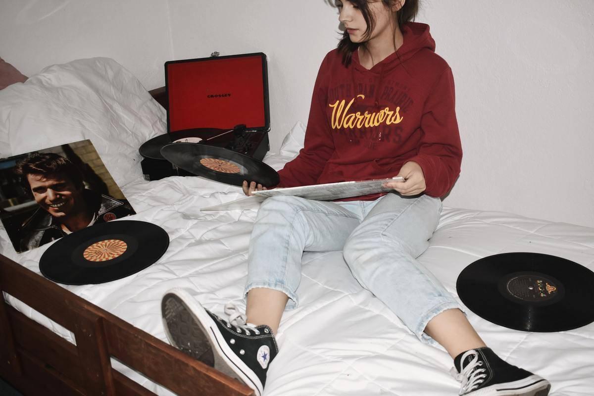 teen girl sitting on bed holding vinyl record