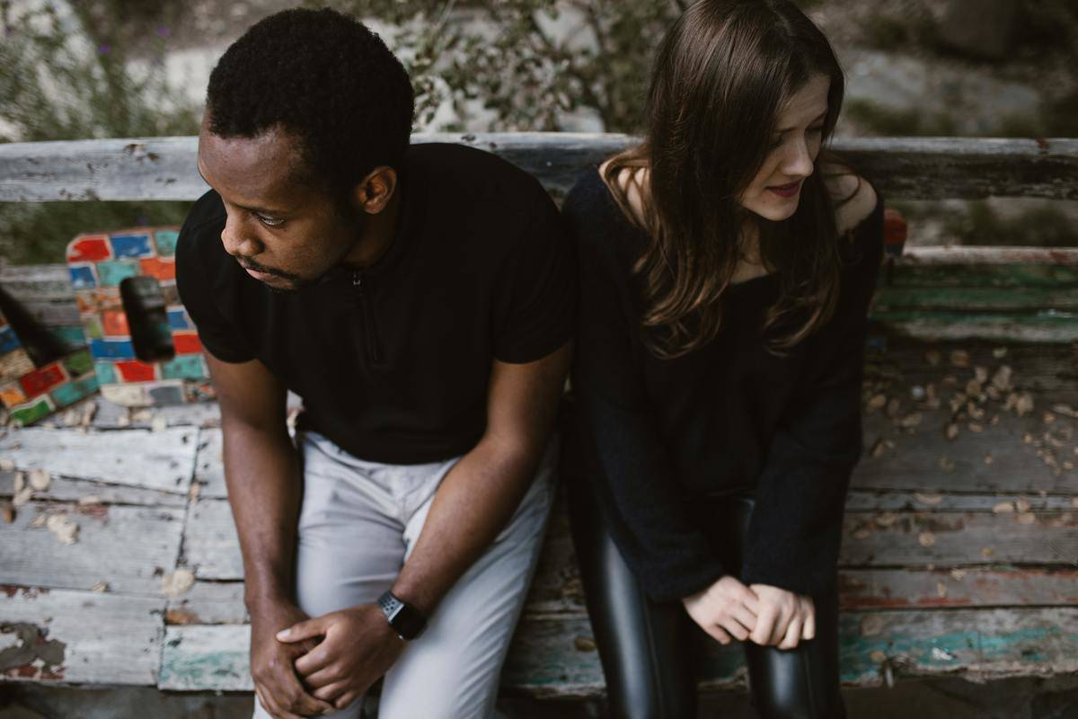 man and woman sitting on bench looking away from each other
