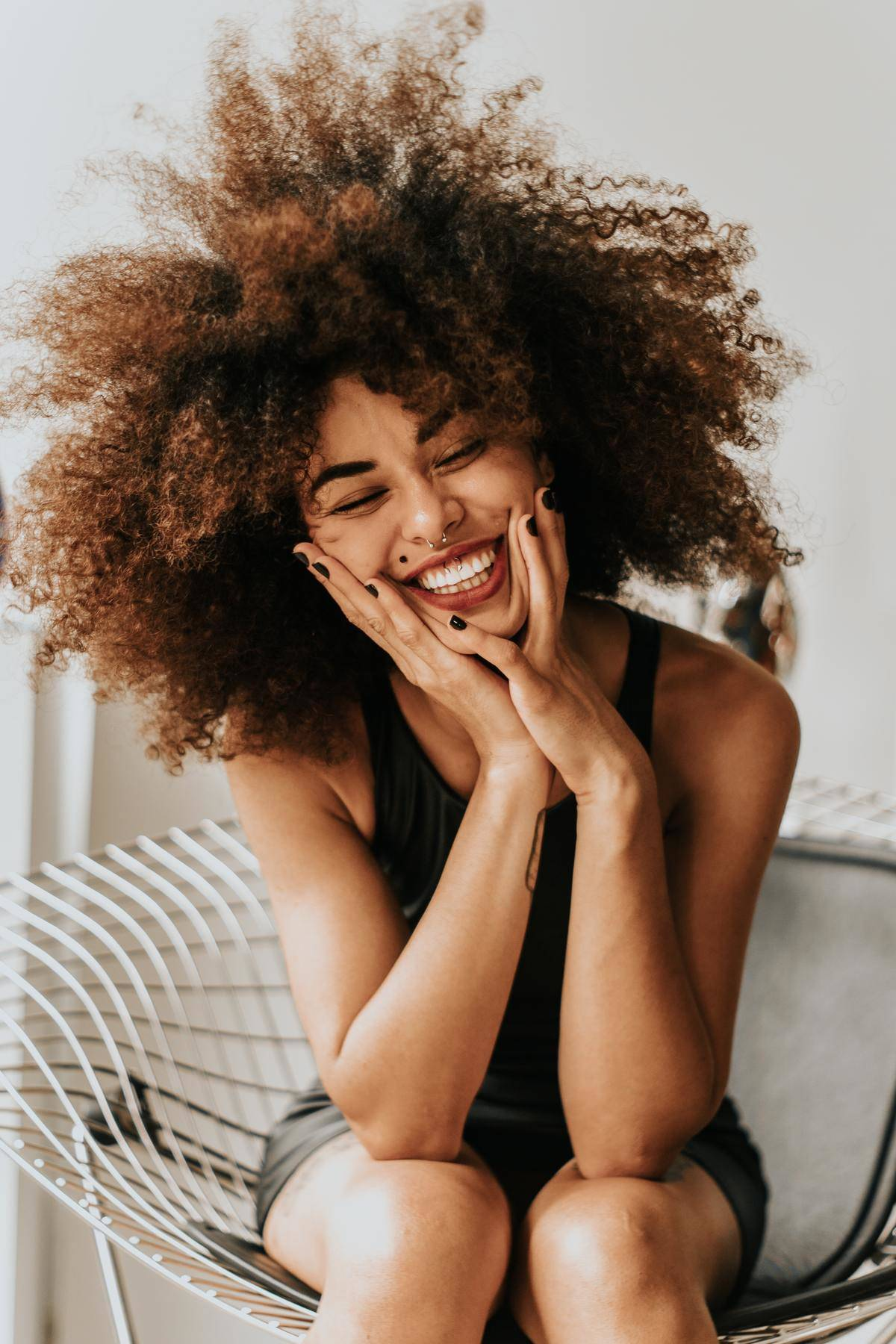 a woman sitting on a chair with a really big smile