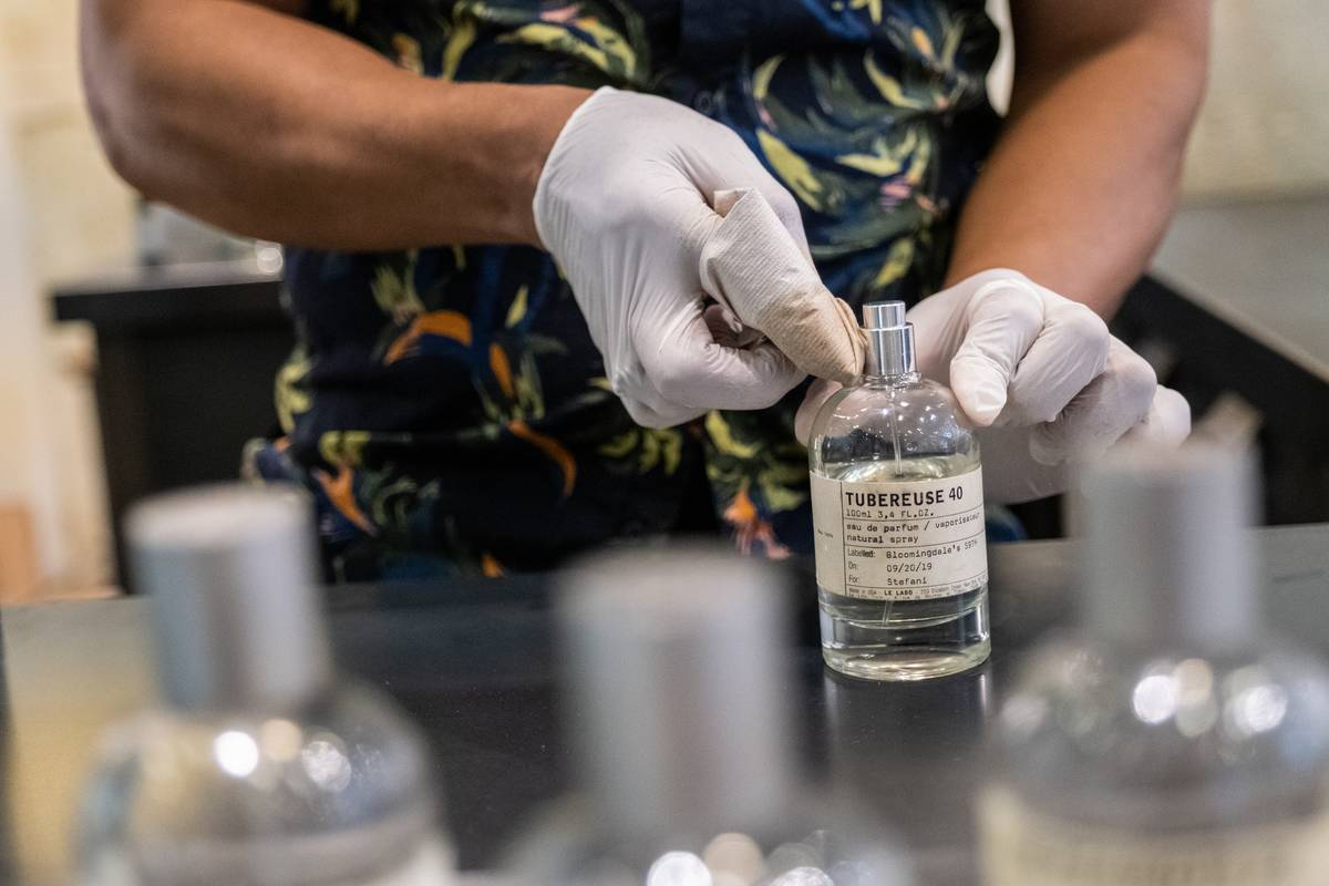 An employee disinfects a perfume bottle top at the Estee Lauder brand Le Labo counter at Bloomingdale's Inc. flagship department story in New York