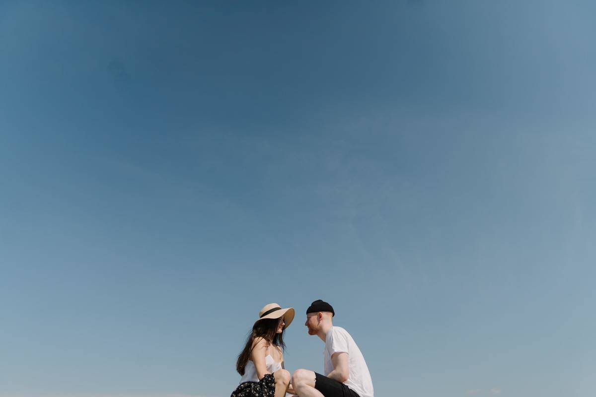 couple sitting on the ground with a big blue sky behind them