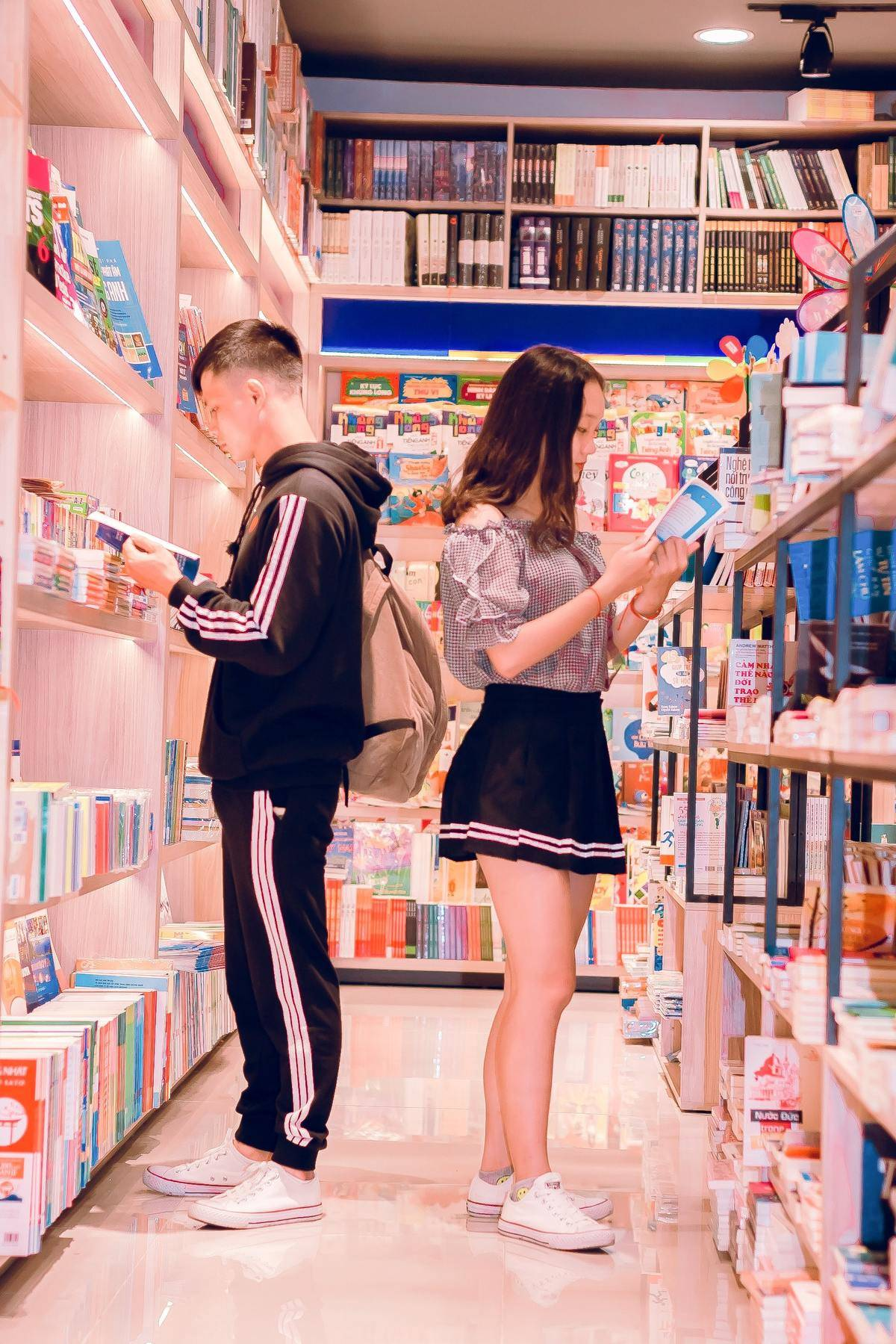 a couple standing in a book store looking at books