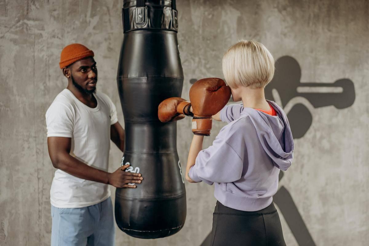 woman hitting punching bag wearing boxing gloves
