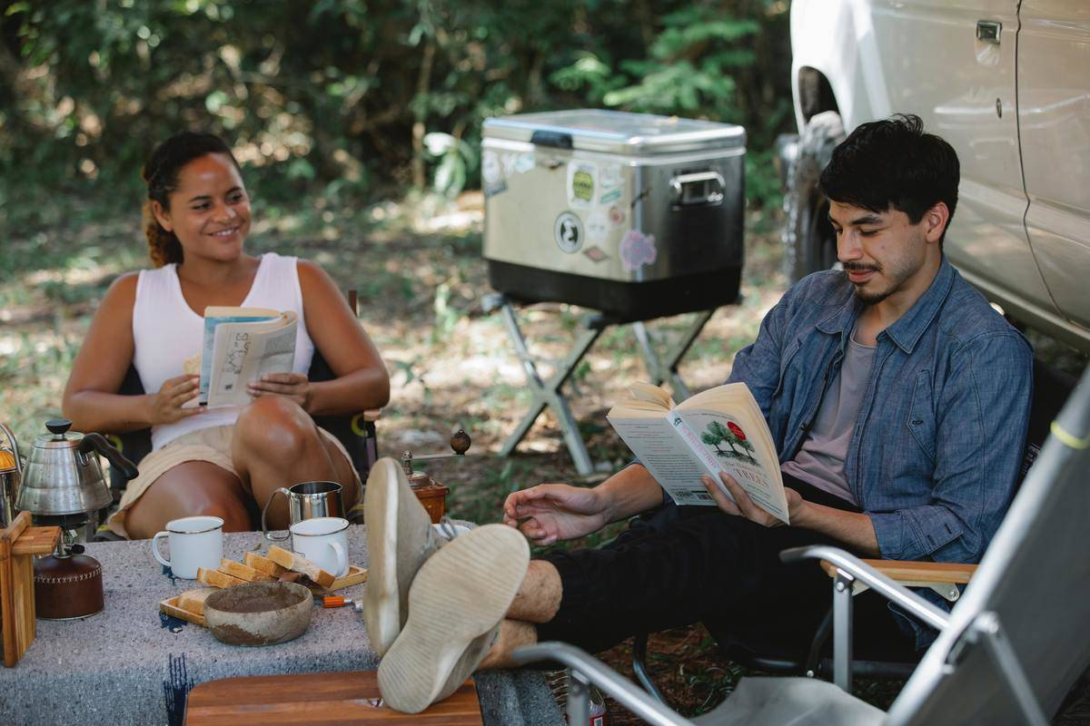 couple sitting outside reading some books at a camp site