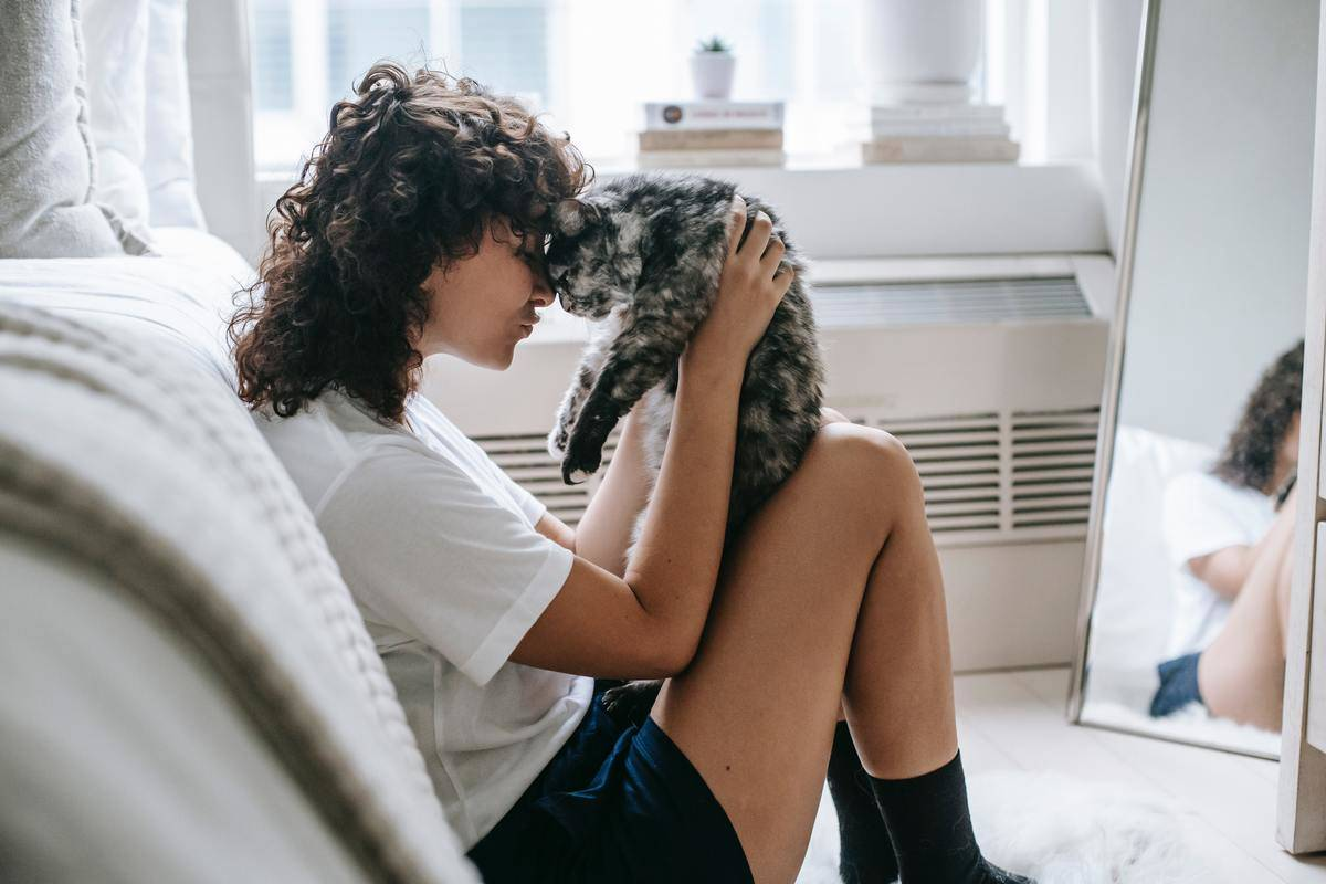 woman holding her cat giving it a hug