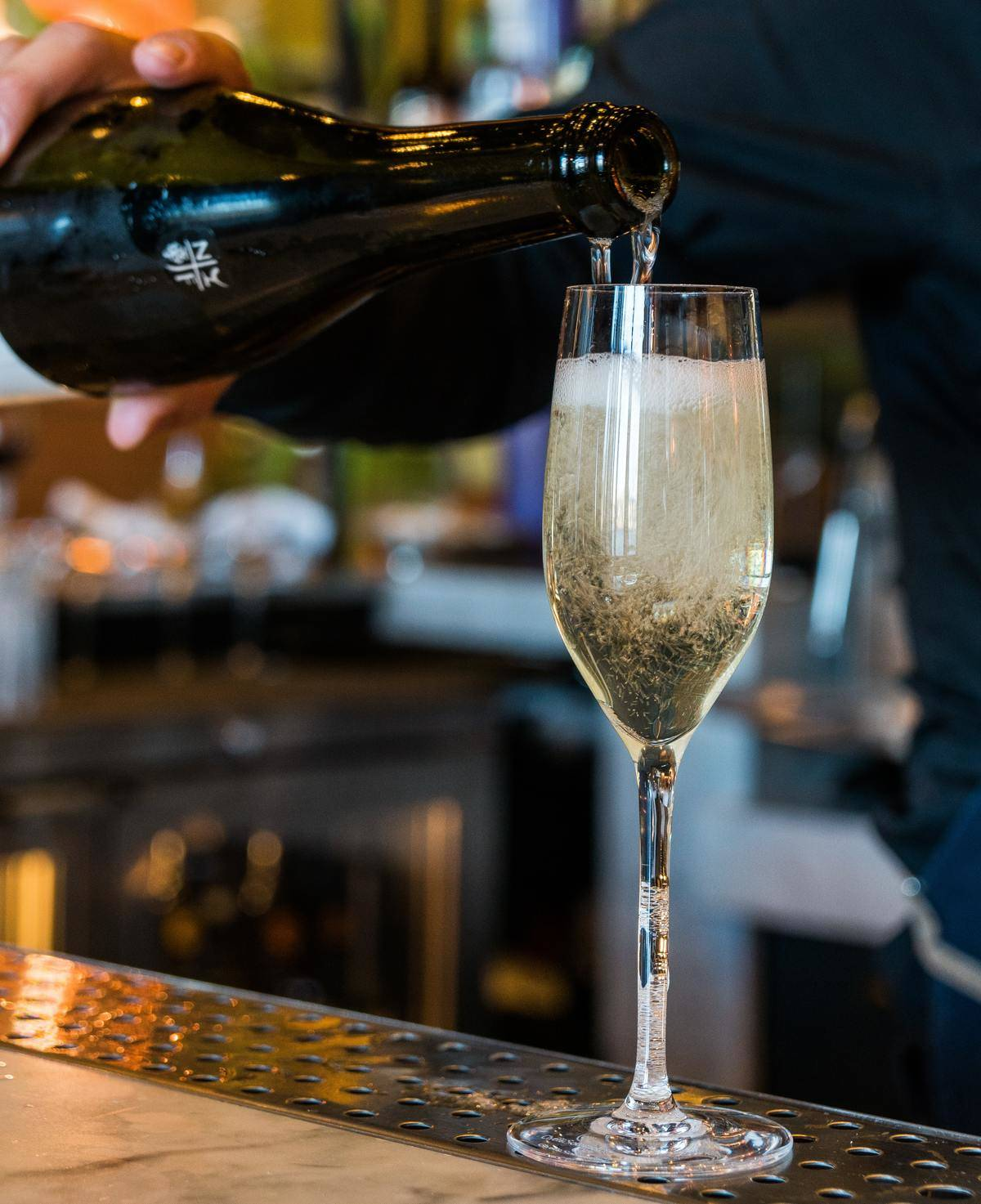 bartender pouring a glass of champagne