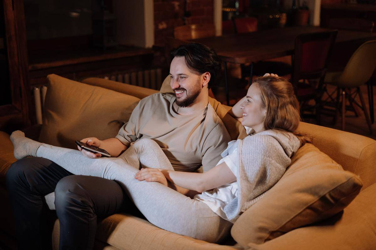 couple sitting on a couch laughing at something on the TV