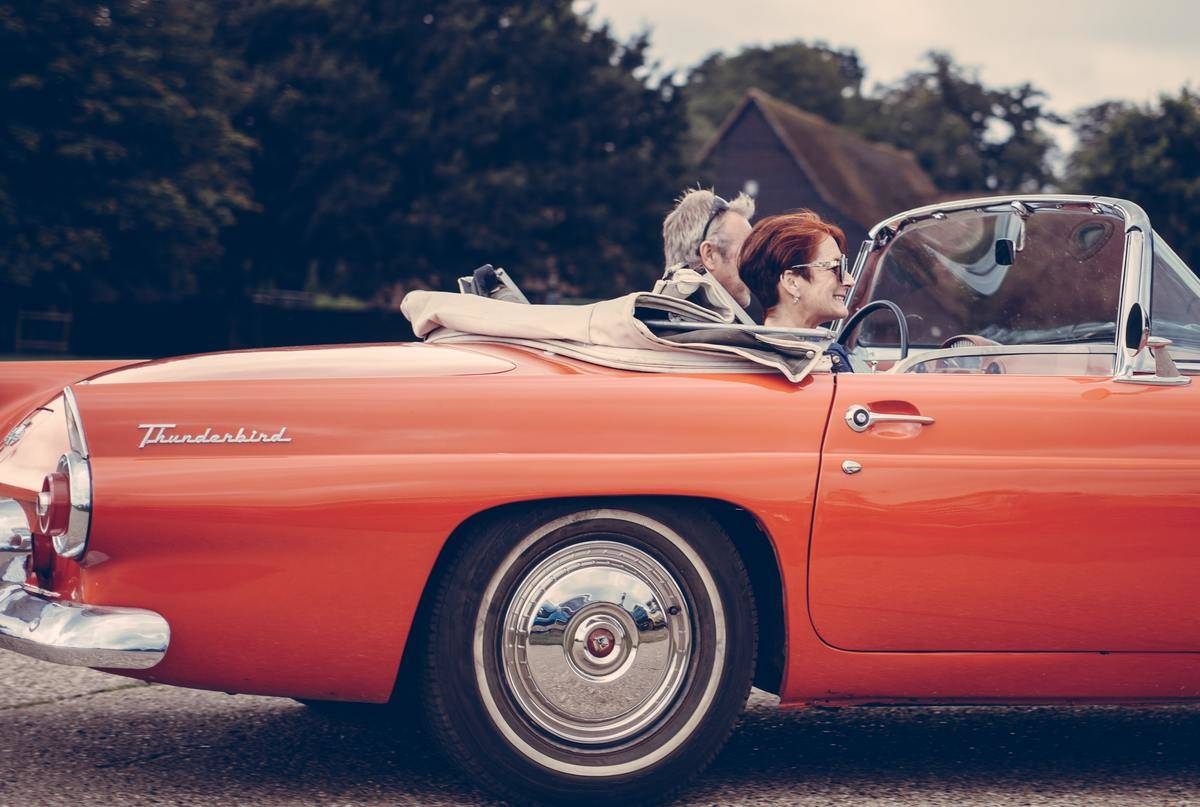 couple driving in orange vintage car