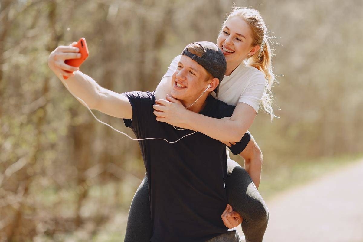 man in black shirt with headphones in taking selfie while giving piggyback to young woman