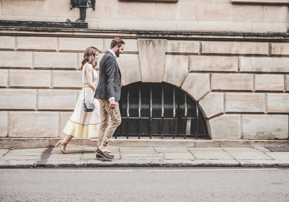 man and woman in nice clothing walking hand in hand on sidewalk