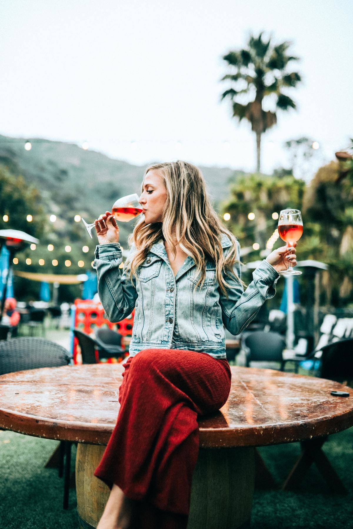 woman sipping from one wine glass while holding another