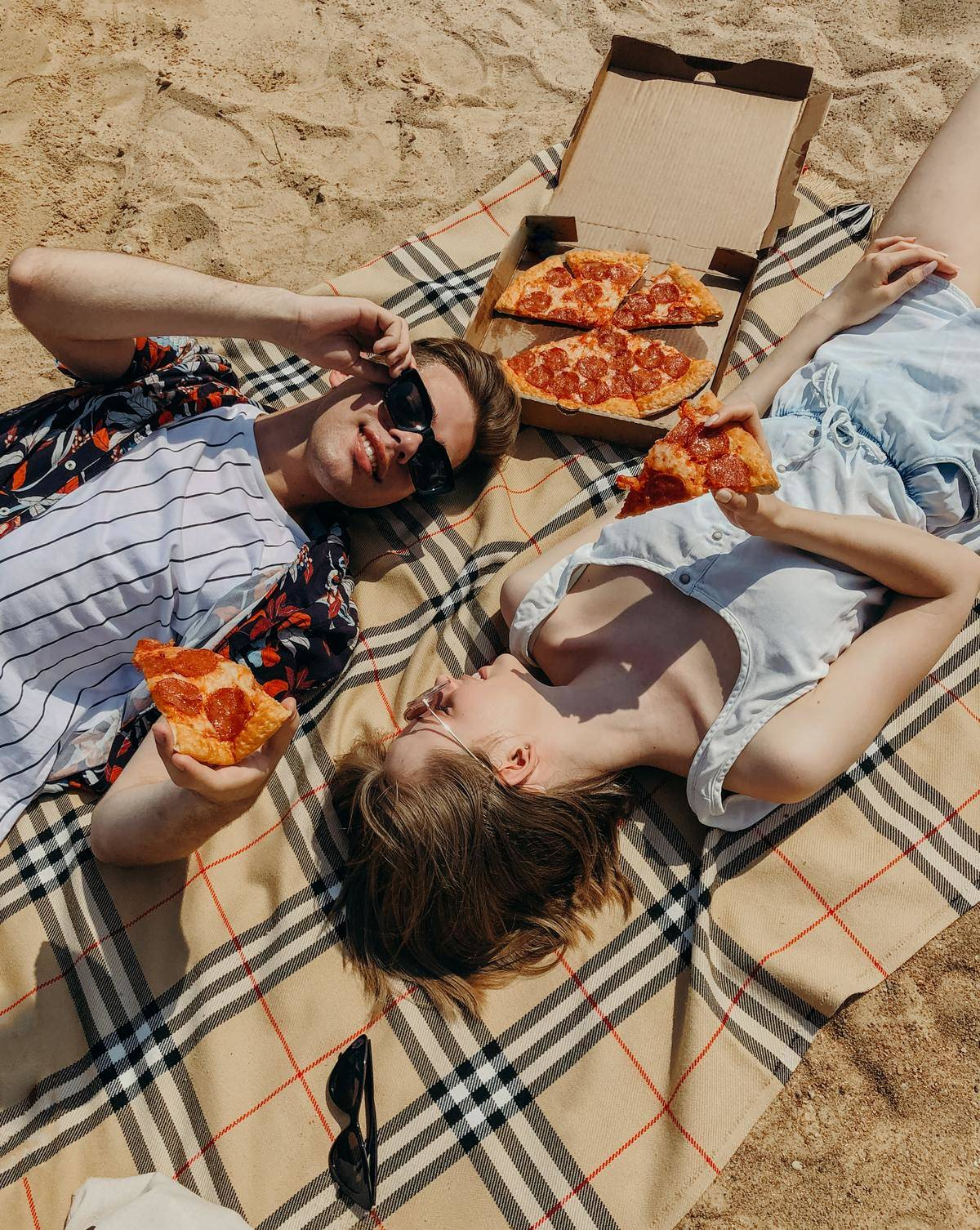 a couple eating pizza on a blanket on the beach