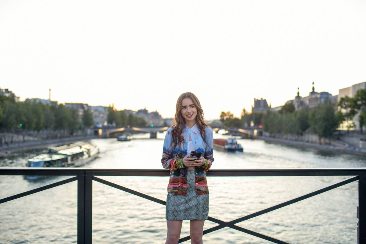still of lily collins standing on a bridge over the Seine in Paris