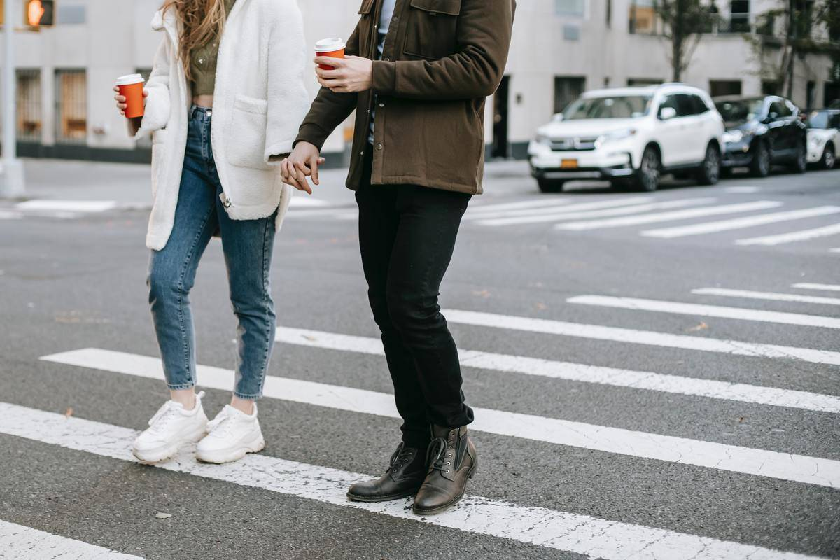 couple walking across the street holding hands with coffee